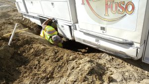 Carman sliding under the Fuso to do a little more digging.